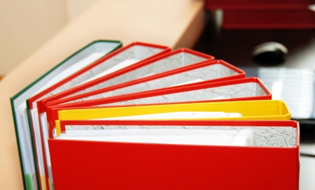 colorful files with documents  on office desk photo