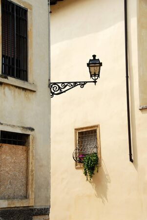 street lamp on building corner and small window, architecture details of Verona, Italy photo
