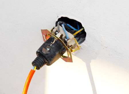electrical jack installed on white wall with plugged cable photo