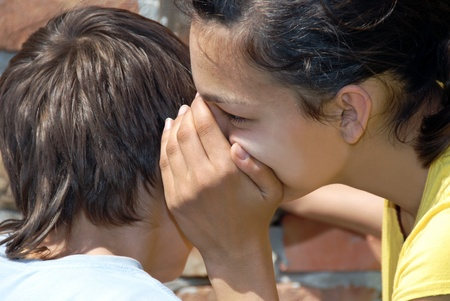 telling: girl telling secret to boy closeup outdoor