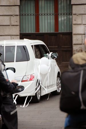 white wedding car with balloons and ribbons on street in Italy photo