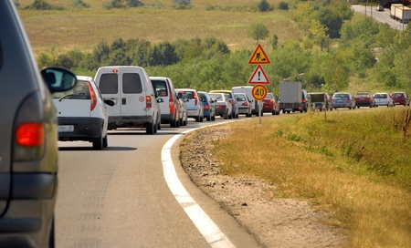 maintains: maintains on country road in Serbia, slow moving cars row and traffic signs