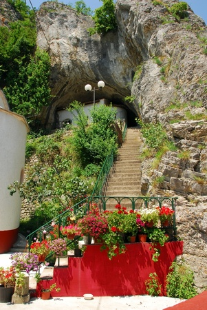 flowerpots: stone stairs into cave in old orthodox Gornjak Monastery in Serbia