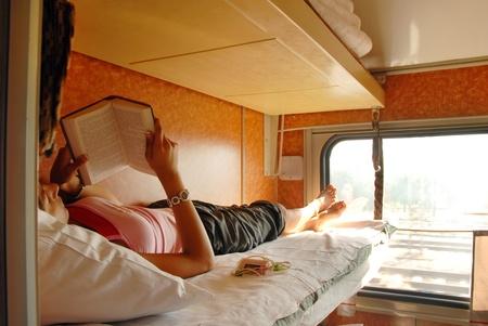 girl lying and reeding a book in sleeping wagon in train photo