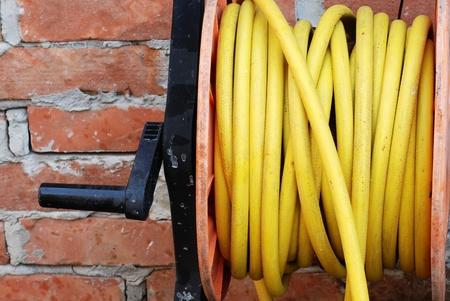 mangera: detalles de la manguera de jardín amarilla en el carrete
