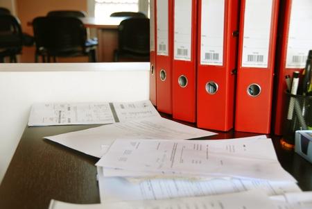 administracion de empresas: oficina de escritorio con carpetas rojas y diversos documentos Foto de archivo