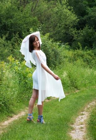 side road: young happy caucasian brunette woman in white dress walking on green rural road