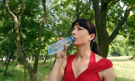 mature brunette: portrait of young caucasian brunette woman with bottle in hand drinking water
