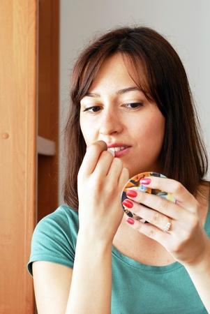 salve: portrait of young caucasian brunette woman applying lip salve Stock Photo