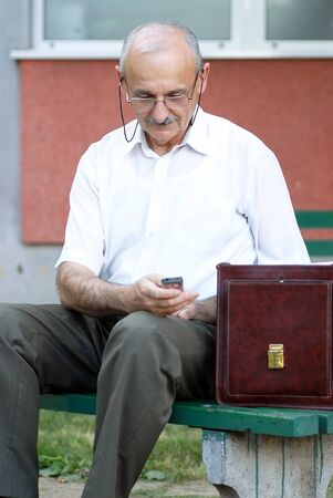portrait of caucasian mature man in glasses with a mobile phone photo