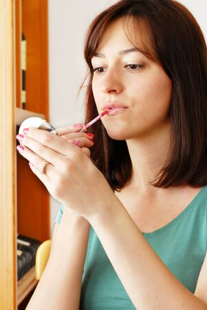 big mouth: portrait of young caucasian brunette woman applying lip gloss