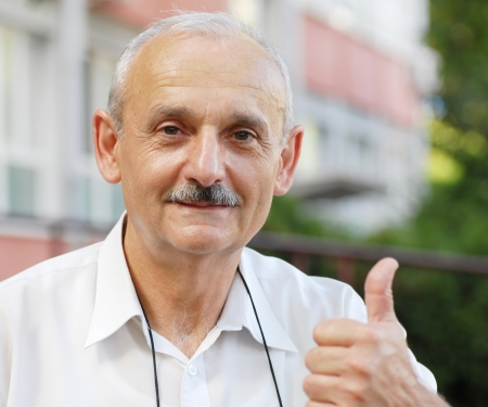 portrait of caucasian mature man with thumb up hand sign photo