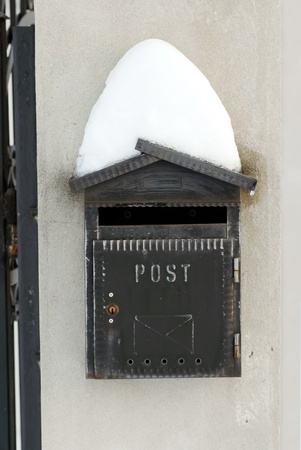 vintage black mail box covered by snow on gray background outdoor photo