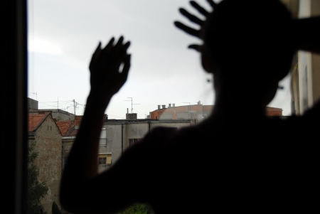 woman black silhouette looking out window indoors, with hands on glass Standard-Bild