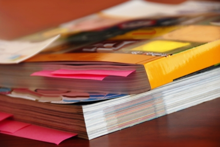 magazine stack: two dense catalogs with bookmarks closeup on desk Stock Photo