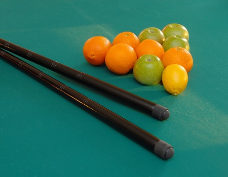 cues: oranges and apples in triangle shape on green billiards table