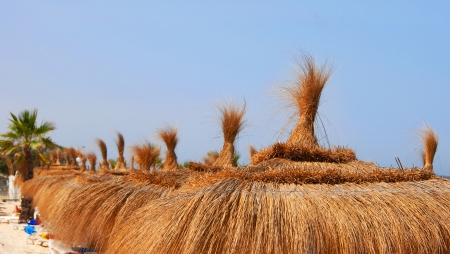 sunshades: natural orange straw sunshades row on beach over blue sky Stock Photo