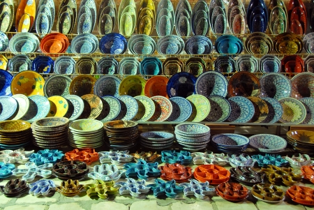 souvenir traditional: various pottery on shelves of oriental outdoor store in Tunisia at the evening