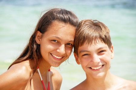 brothers and sisters: portrait of two teenagers boy and girl smiling at seaside at summer
