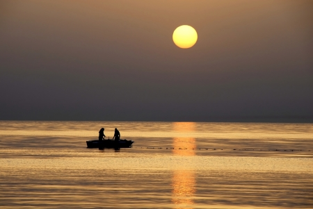 rising: silhouettes of two fishermen fishing in boat on sea at gorgeous sunrise in Tunisia