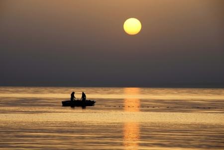 sol naciente: siluetas de dos pescadores de pesca en barco en el mar al amanecer precioso en Túnez Foto de archivo