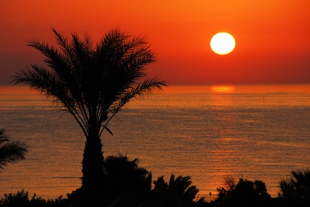 early summer: gorgeous  sunrise over tranquil sea water and orange sky in Tunisia Stock Photo