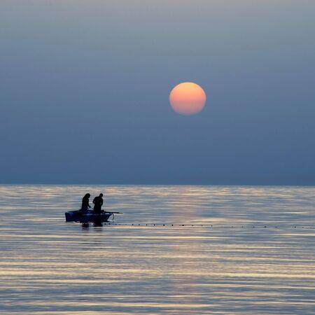 redes de pesca: siluetas de dos pescadores de pesca en barco en el mar al amanecer precioso en T�nez Foto de archivo