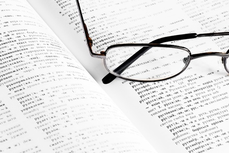 linguistics: opened russian-serbian dictionary book with eye glasses Stock Photo