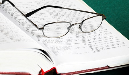 opened russian-serbian dictionary book with eye glasses Standard-Bild