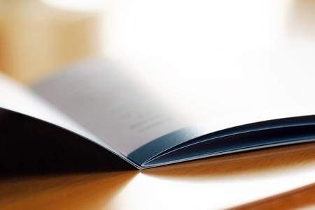 茶色の机マクロで開かれたパンフレットのクローズ アップ 写真素材