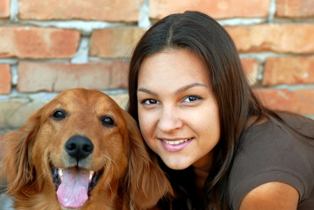 portrait of young caucasian teenage girl with her golden retriever dog photo