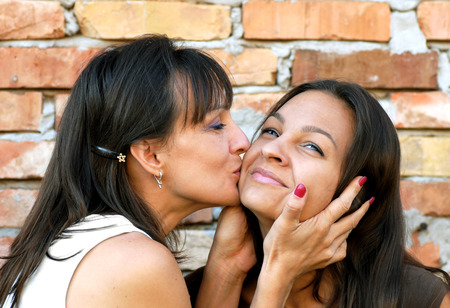 madre e hija adolescente: retrato de la madre besando a su hija adolescente sonriente Foto de archivo