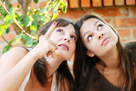 madre e hija adolescente: madre mirando hacia arriba y muestra su hija adolescente algo por encima de Foto de archivo