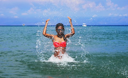 ionic: slim caucasian teenage girl with raised hands splashing water in the blue Ionic sea, Greece Stock Photo