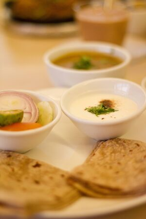 Various Vegetarian Dishes - Yoghurt, Dhal Bean Curry, Chapattis (Indian Cuisine)
