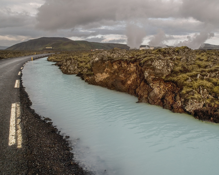 grindavik: Silica rich blue green river running alongside a road outside of the Blue Lagoon Spa in a lava rock green mossy field in Iceland.