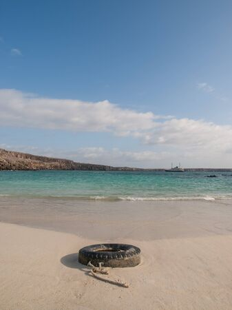 shore line: Black spare tire and rope laying on empty beach by the shore line with a ship and blue sky with clouds in the background in Galapagos Islands Ecuador.
