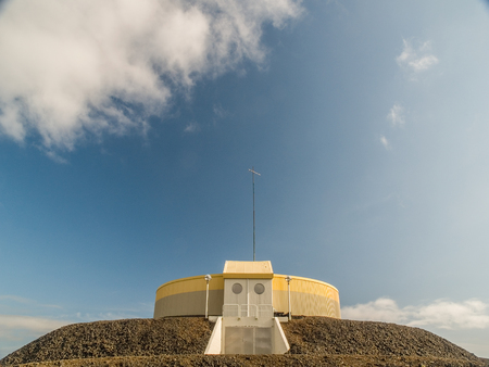 grindavik: Circular industrial yellow and gray building on top of gravel platform against a blue sky with clouds near Keflavik Iceland.