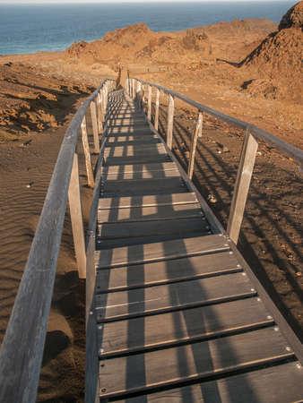 bartolome: Wooden plank boardwalk with railing climbing uphill to a viewing platform on Bartolome, Galapagos Islands, Ecuador.