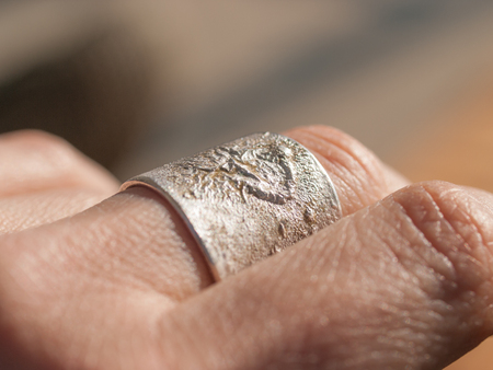 artisanal: Artisanal silver ring close up on middle finger of womans hand. Ring made by Aaron Maya. Stock Photo
