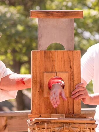 guillotine: Two caucasian men standing beside a hand guillotine with one hand ready to be cut off. Both are wearing white shirts and one arm has blood on it. Outdoors with green trees in the backgound during the day.