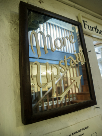 upstairs: Brown wooden framed mirror with painted on cursive letters saying More Upstairs with arrow at an antique thrift store in Hay-on-Wye, Wales, United Kingdom, Europe.