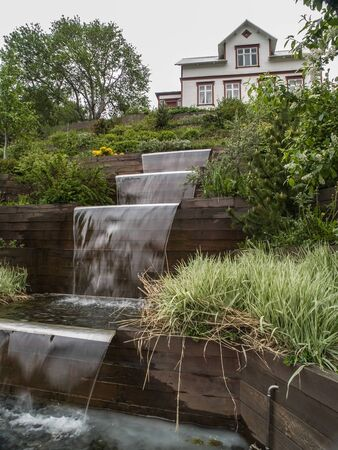 cascading: Cascading pond in landscaped garden in front of white house in Akureyri, Iceland. Stock Photo