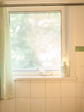 shower stall: Bright single pane window surrounded by white tiles in a shower stall in a residential home.