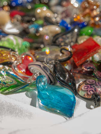 white linen: Variety of colourful glass pendents for sale on a table with white linen cloth.