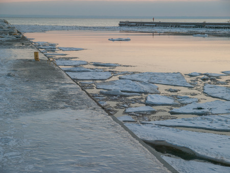 ice covered: Ice covered pier and Lake Ontario at sunset in winter in Oakville, Ontario, Canada.