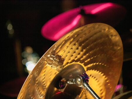 cymbals: Back of one gold drum cymbal and another cymbal lit up with pink lights. Stock Photo