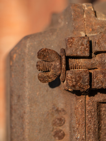 metal fastener: Rusty wing nut and bolt fastened in wall. Stock Photo