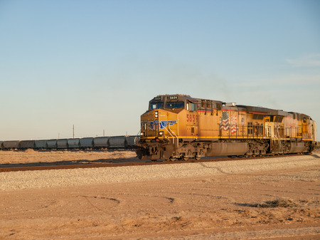 Yellow train with American flag travelling on a bend against a blue sky in the sandy desert in California, USA.