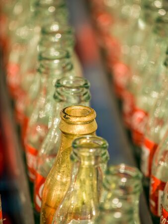 to toss: Lines of clear empty coke bottles, where only a few are painted gold, for a ring toss game at the Canadian National Exhibition in Toronto, Ontario, Canada.